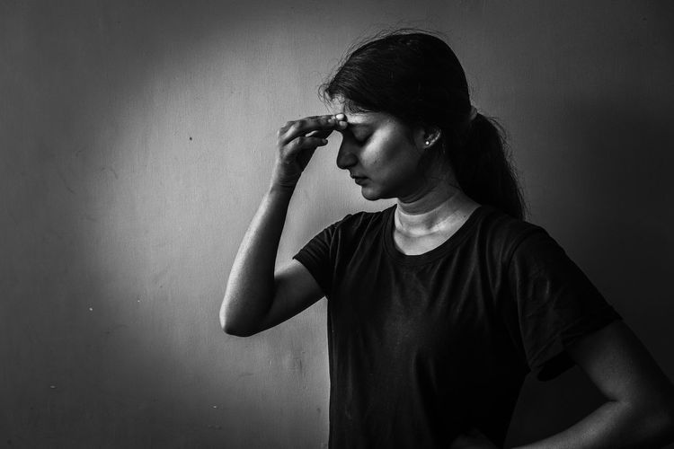 Depressed woman standing by wall at home