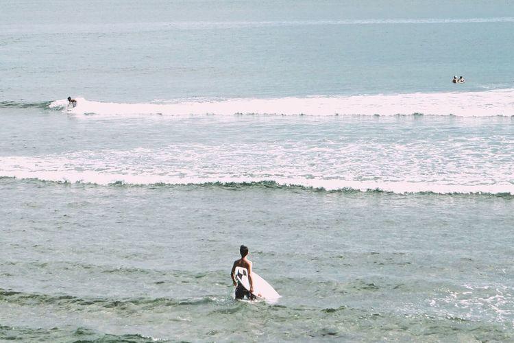 Man With Surfboard Walking In Sea Against Sky
