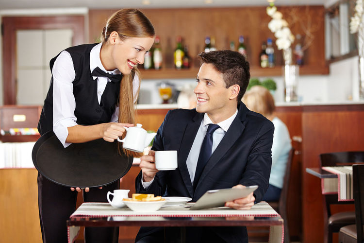 Young man holding coffee cup on table in restaurant