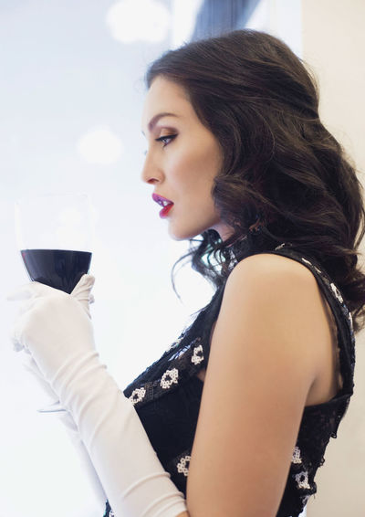Side view of young woman holding drink