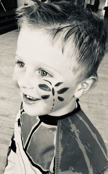 Cute boy with painted cheek at home