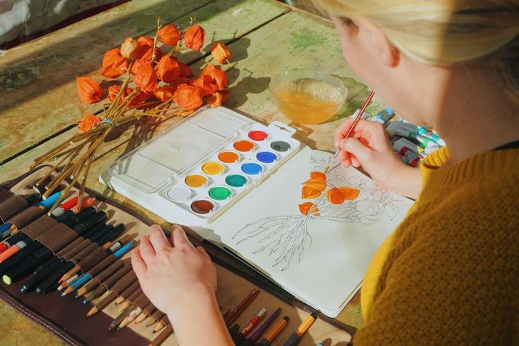 Midsection of female artist painting flowers in notebook