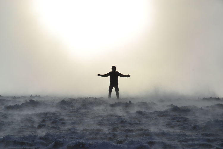 Silhouette man with arms outstretched standing in fog against sky