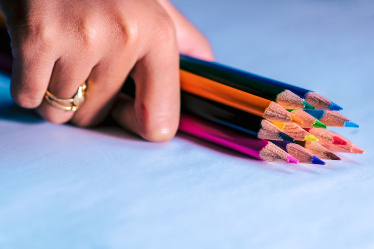 Close-up of human hand against colored pencils