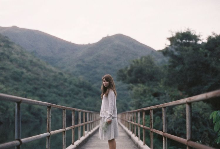 Young Woman Standing On Footbridge Against Mountain