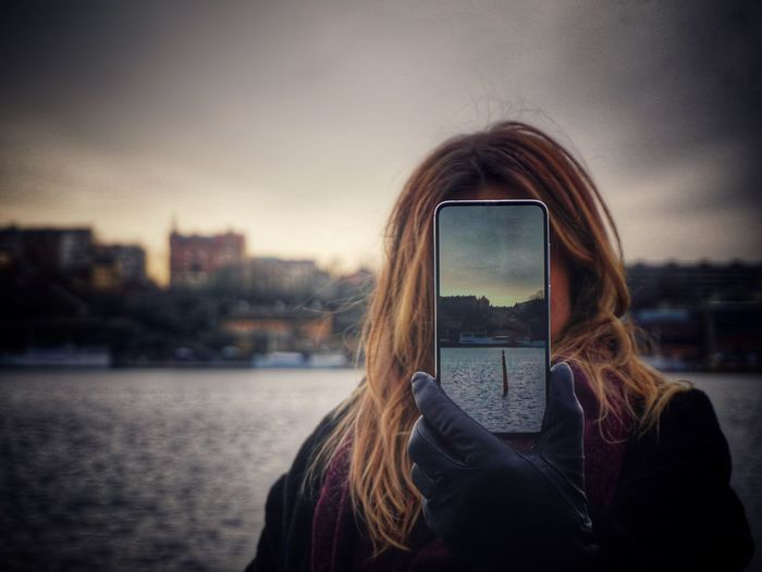 Portrait of woman photographing against sky in city