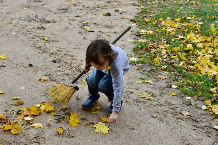 High angle view of boy holding broom and autumn leaves