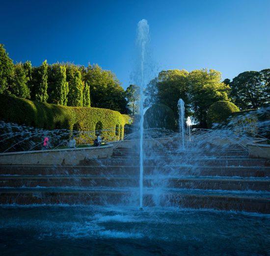 Water splashing in fountain against sky