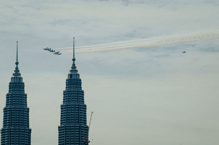 Air Show Air Vehicle Airplane Airshow Architecture Business Finance And Industry City Cityscape Cloud - Sky Day Flying Military Airplane No People Outdoors Sky Skyscraper Travel Vapor Trail Vapor Trails
