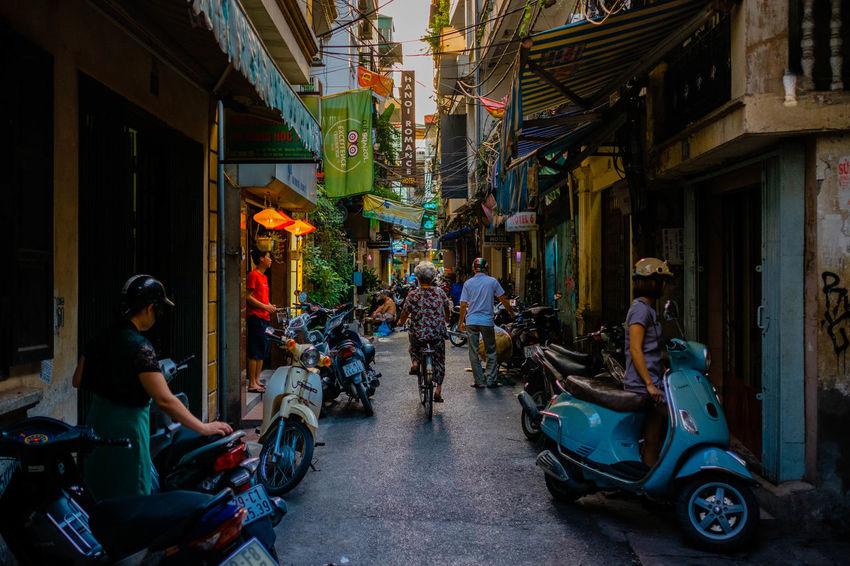 Back alley vibes. Adult Architecture Building Exterior Built Structure City Group Of People Land Vehicle Leisure Activity Lifestyles Men Mode Of Transportation Motion Motor Scooter Motorcycle Outdoors People Real People Scooter Street Transportation Women