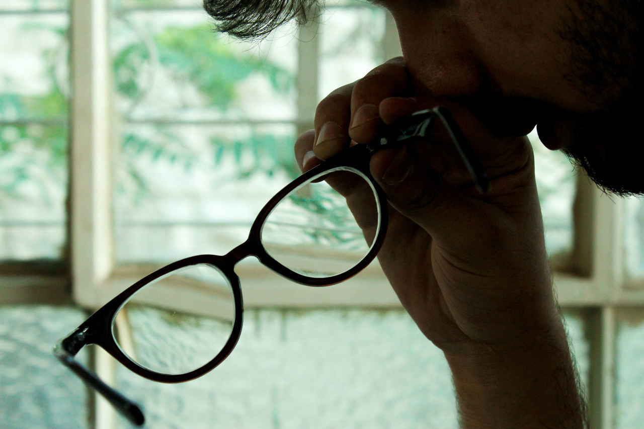 one person, holding, indoors, human hand, eyeglasses, focus on foreground, human body part, day, close-up, men, real people, eyesight, one man only, technology, eye test equipment, people