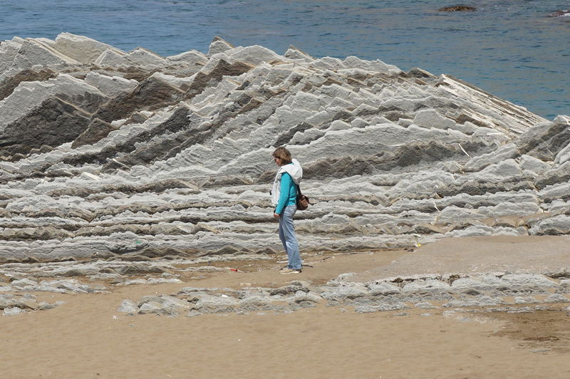Side view of woman standing amidst flysch rocks at beach on sunny day