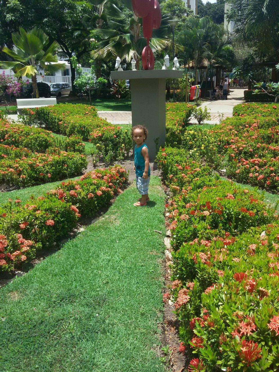 Baby Boy Standing By Sculpture Amidst Plants At Park