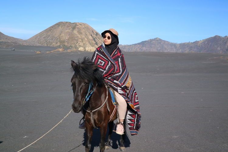 Woman riding horse at desert against sky