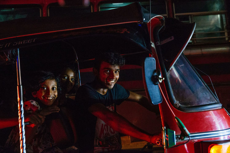 The streets were bustling and writhing with energy in Galle as Sri Lankans celebrated Vesak, the day of Buddah. Shooting from a Tuk Tuk in low light is extremely difficult in ever changing circumstances with light shifting every time traffic moves. Commuter Happiness Sri Lanka Sri Lanka 🇱🇰 The Street Photographer - 2018 EyeEm Awards The Traveler - 2018 EyeEm Awards Enjoyment Front View Land Vehicle Looking At Camera Mode Of Transportation Motor Vehicle People Portrait Smiling Street Photography Transportation Tuk Tuk