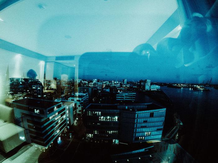 High angle view of illuminated city seen through window