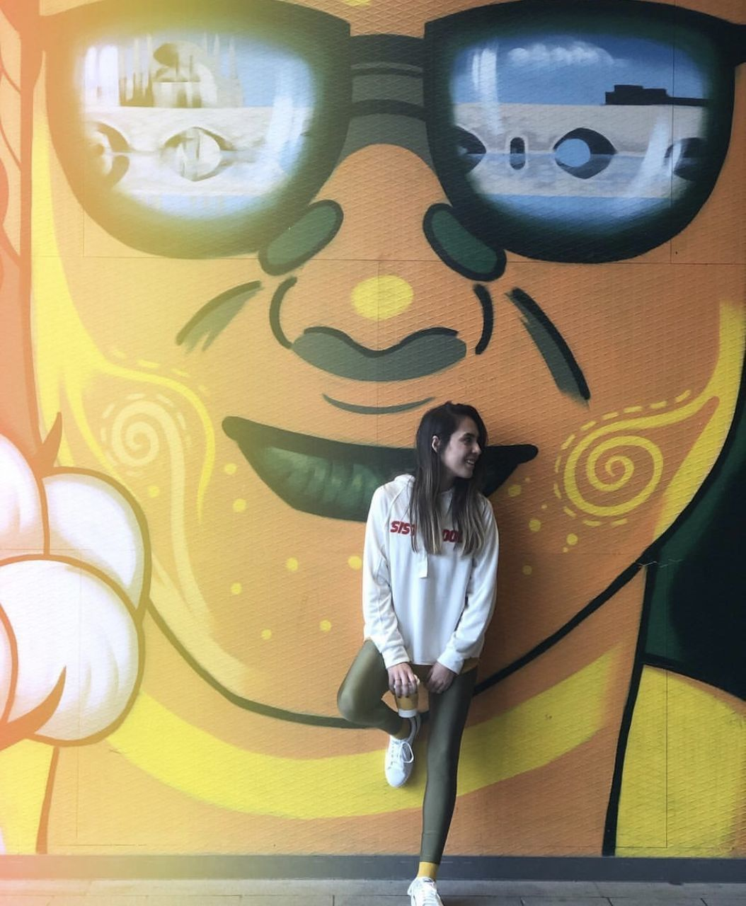 one person, real people, lifestyles, front view, casual clothing, leisure activity, young women, indoors, young adult, portrait, wall - building feature, standing, looking at camera, graffiti, women, adult, clothing, wall, hairstyle, mural