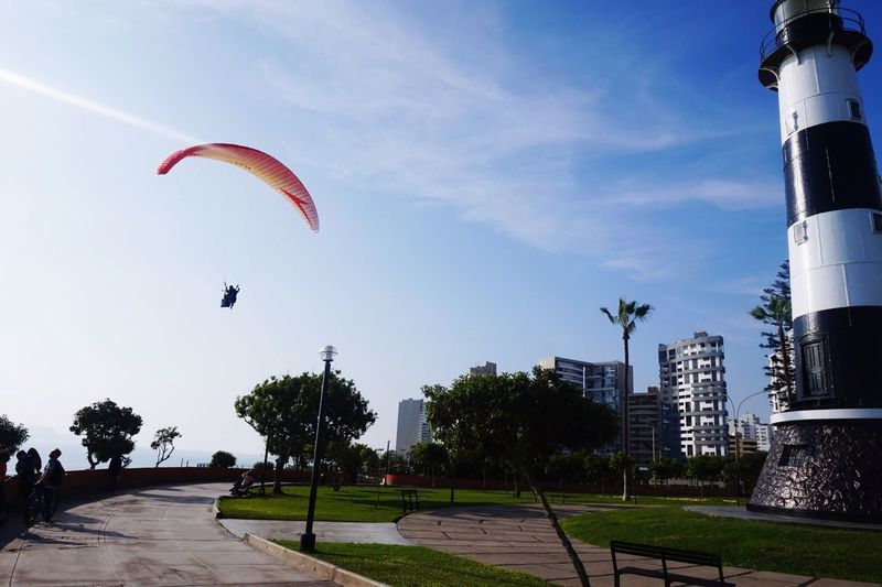 Leisure Activity Adventure Extreme Sports Sky Outdoors Real People Lifestyles Parachute Day Sport Tree Architecture One Person Paragliding Flying Nature City People EyeEmNewHere Perspectives On Nature