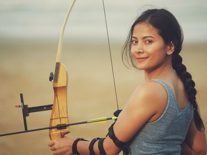 Bow Archery Real People One Person Portrait Lifestyles Leisure Activity Young Adult Looking At Camera Adult Headshot Smiling Females Young Women Women Hairstyle Nature Focus On Foreground Holding