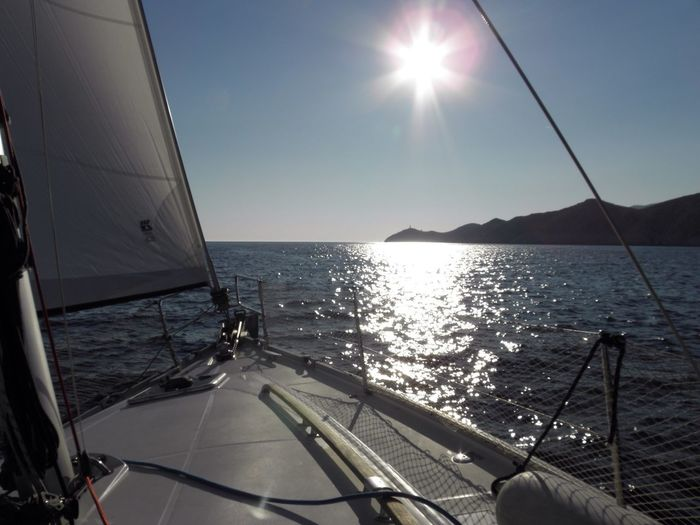 Sea Sunlight Nautical Vessel Sun Sailing Water Horizon Over Water No People Sunbeam Nature Beauty In Nature Boat Deck Outdoors Sailboat Day Sky Yacht Yachting Sailing Ship Marine Life Vacations Sunset Island Cruise Navigation