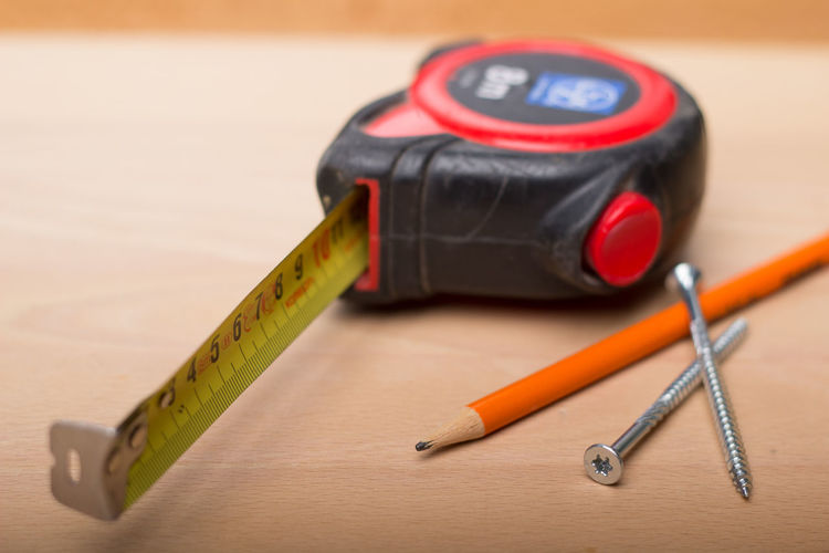 Close-Up Of Tape Measure And Pencil On Wooden Table