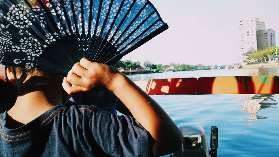 Rear view of child holding folding fan against sea in city