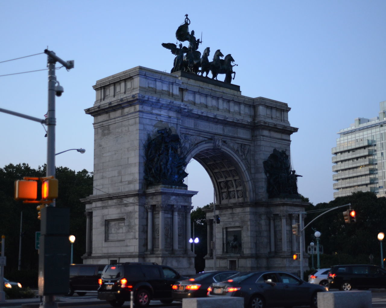statue, architecture, built structure, human representation, car, sculpture, triumphal arch, city, arch, travel destinations, outdoors, building exterior, low angle view, travel, history, sky, illuminated, day, real people, clear sky