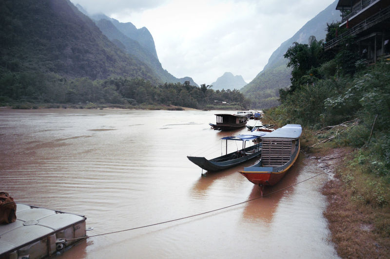 Laotian boats moored on riverside in muang ngoy village