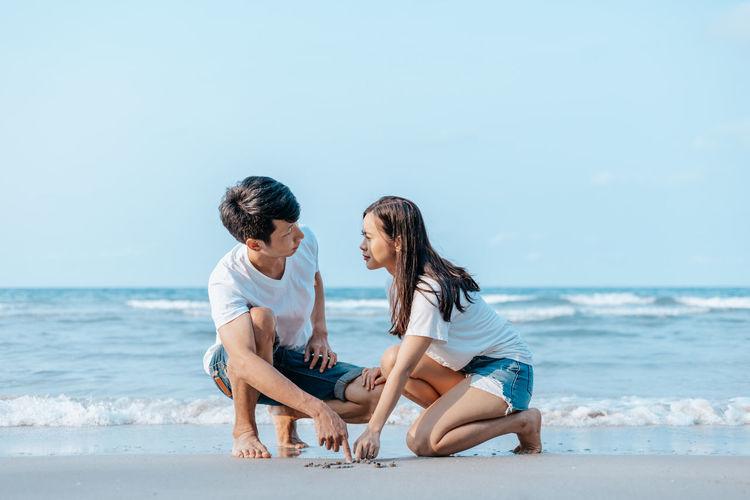 Friends sitting on beach against sea
