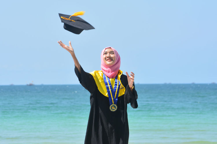 Woman in hijab looking at mortarboard while standing against sea
