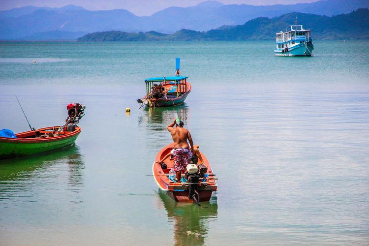 Man pouring water over body on a hot day. ระนอง ประเทศไทย ท่องเที่ยวไทย ท่องเที่ยว เกาะพยาม ทะเล ภูเขา ชาวประมง ชาวเกาะ ชาวเล วิถีชีวิตคนไทย วิถึชาวเล เรือ ชีวิตประจำวัน Islander Reflection Lifestyle Daily Life Kohphayam Sea Boat Thailand Ranong Occupation Fisherman Mountain Sky Longtail Boat
