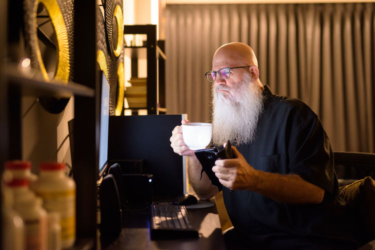 Man holding coffee cup on table