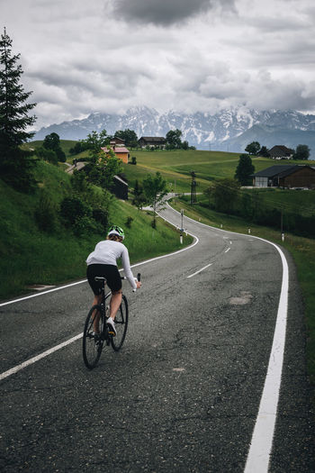 Woman riding her roadbike on road in the austrian alps under dramatic sky
