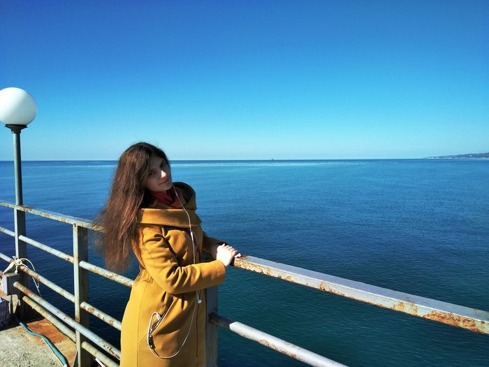 Beautiful woman standing by railing on pier against sea