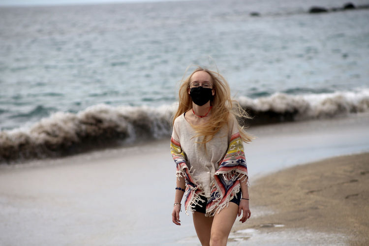 Full length of woman wearing sunglasses on beach