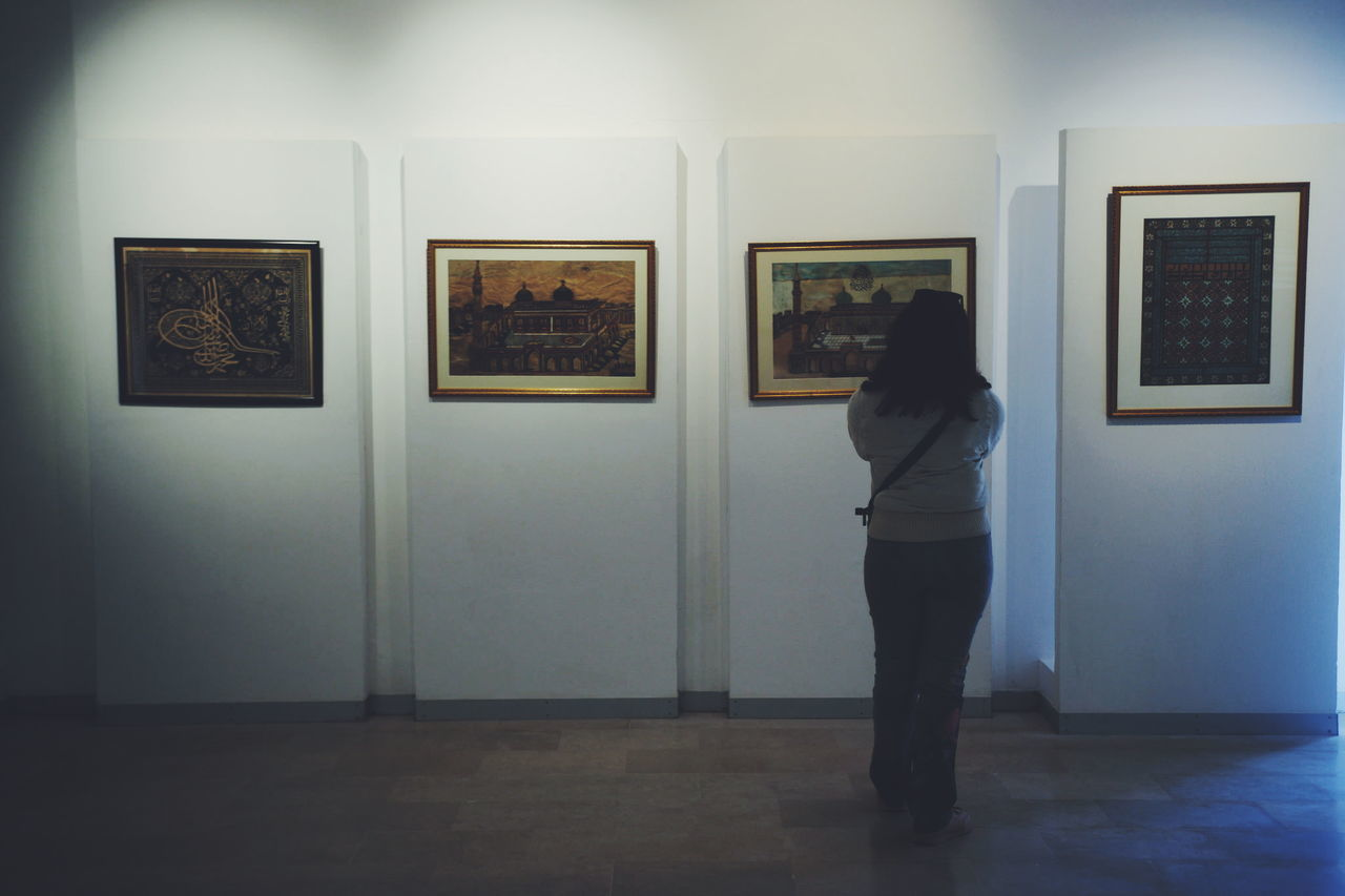 one person, standing, indoors, museum, frame, real people, full length, rear view, picture frame, women, lifestyles, paintings, adult, art museum, architecture, wall - building feature, leisure activity, art and craft, exhibition, flooring, hairstyle