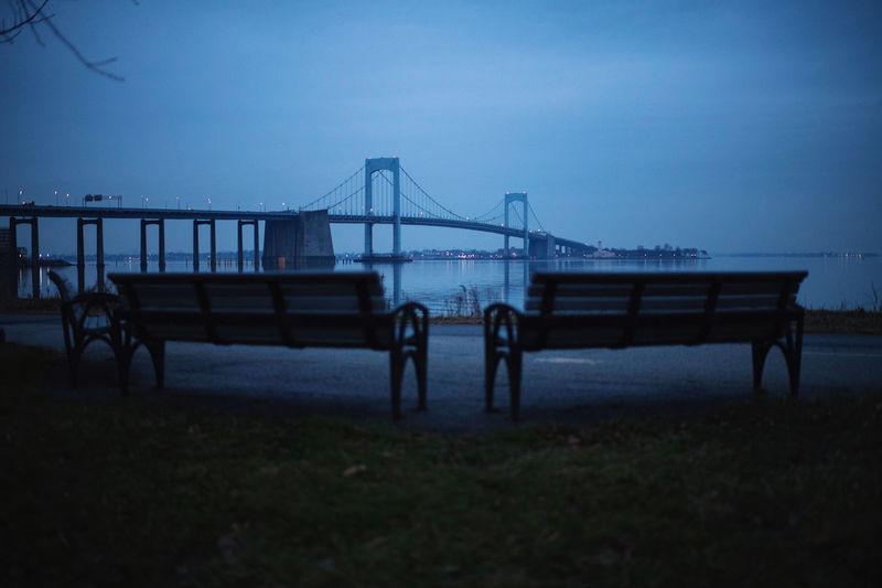 Bridge in field against sky at dusk