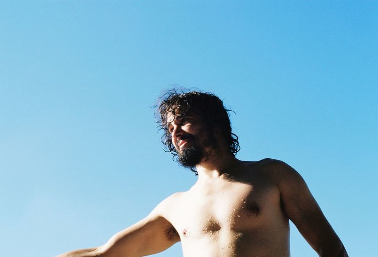 Low angle view of shirtless man standing against clear blue sky