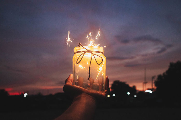 Cropped hand holding burning sparklers in container against sky at night