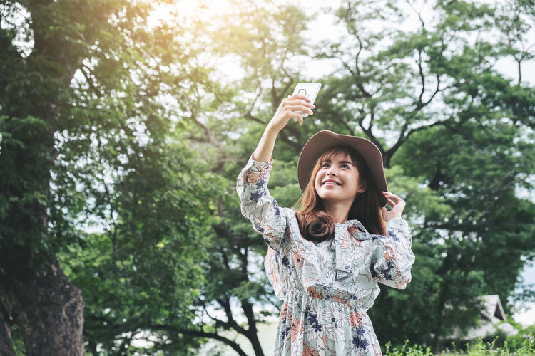 Holiday Arms Raised Beautiful Woman Casual Clothing Day Focus On Foreground Front View Hairstyle Happiness Human Arm Leisure Activity Lifestyles Nature One Person Outdoors Plant Portrait Real People Selfie Smiling Standing Tree Women Young Adult Young Women
