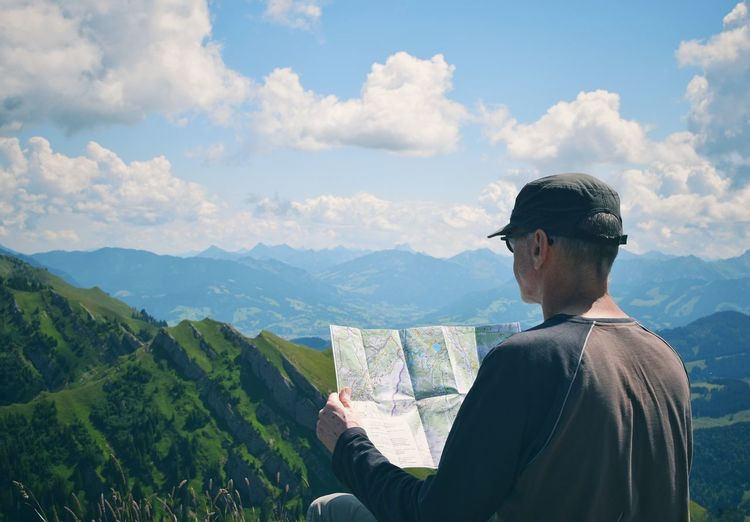 Rear view of man holding map with mountains in background against sky