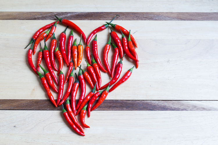 Space For Text Natural Light Red Food Food And Drink Still Life Table Freshness Healthy Eating Vegetable Wellbeing Pepper Directly Above No People Chili Pepper Indoors  Spice Red Chili Pepper Close-up Spicy Cuisine Ingredient Heart-shaped Diet Raw Food