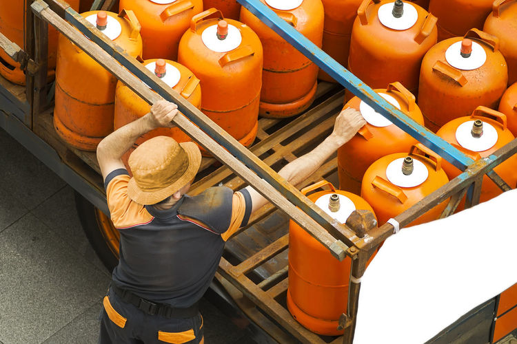 High angle view of man picking lpg cylinder from truck