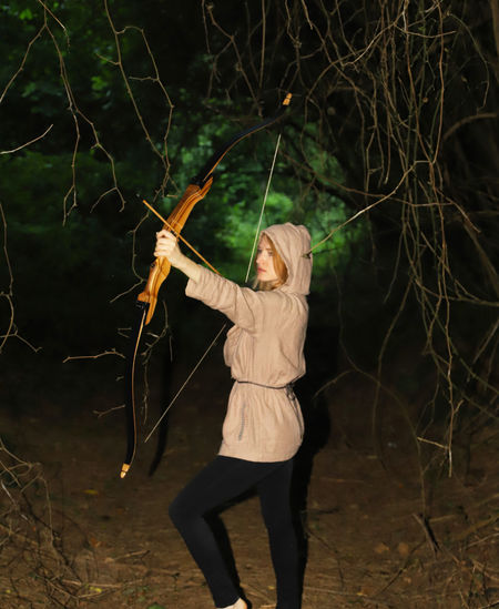 Young Woman Holding Bow And Arrow While Standing In Forest