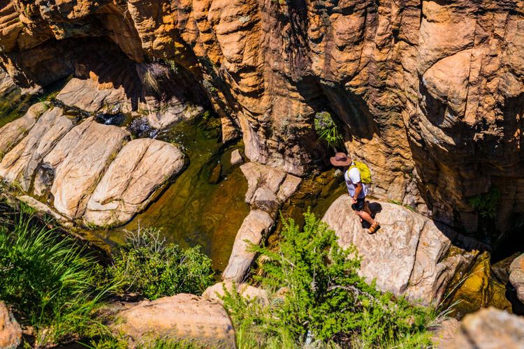 High angle view of man standing on rock at mountain sanctuary park