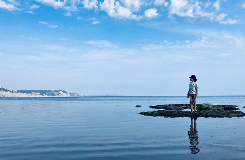 Full length of boy standing on rock against sea and sky