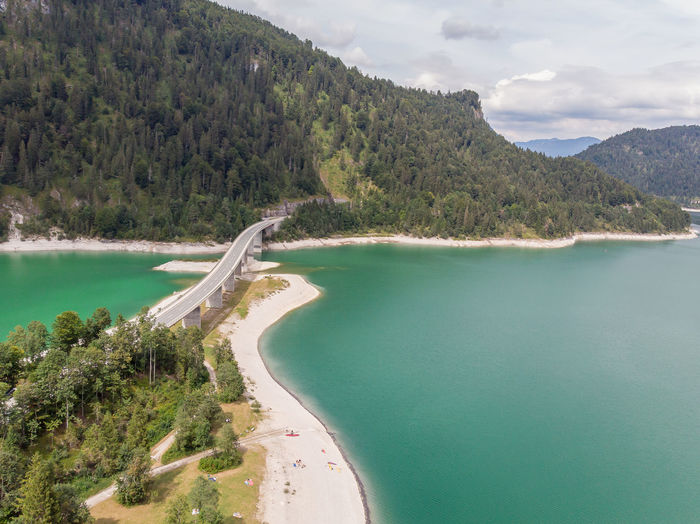 Drone view of the artificial Sylvenstein-Lake Dronephotography Drone  Aerial View Bavarian Alps Alps Lake Lake View Water No People Beach Coastline Non-urban Scene Turquoise Colored Environment Bay Idyllic Bridge - Man Made Structure Dynamic Lines Road The Way Forward The Week on EyeEm Mountain Forest Mystery
