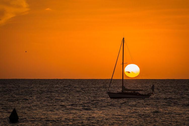 Silhouette boat on beach against orange sky