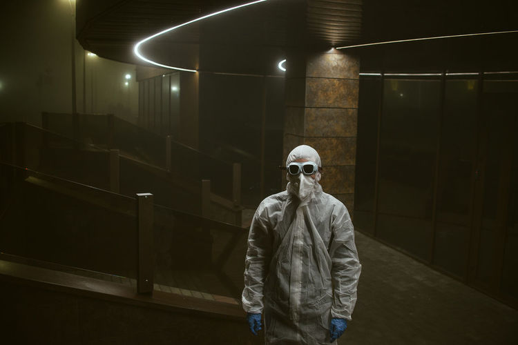Man standing in protective suit in building