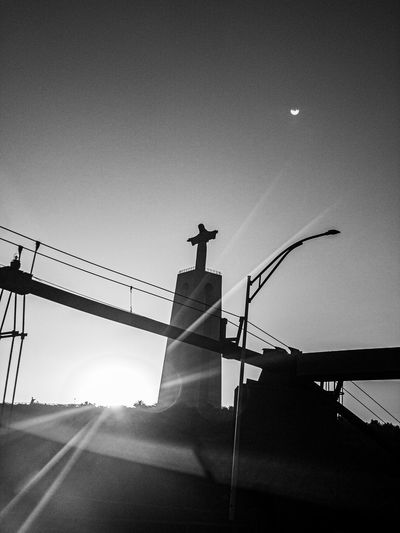 Low angle view of silhouette cross against sky